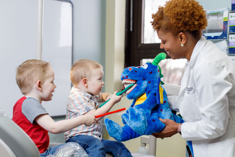 A dentistry professional holds a stuffed dragon as two young children brush its teeth.
