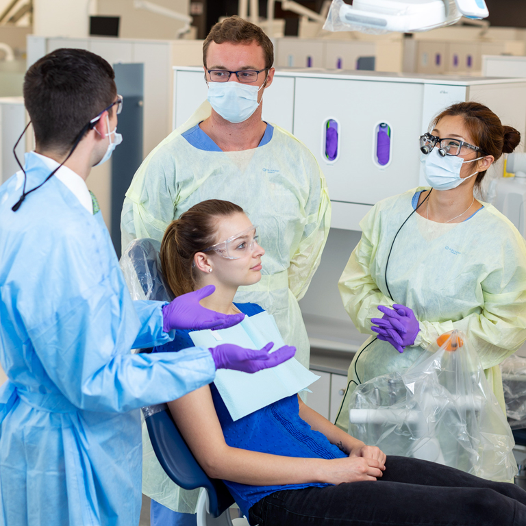 Three dentistry professionals talk as they stand around a young woman sitting in an exam chair.